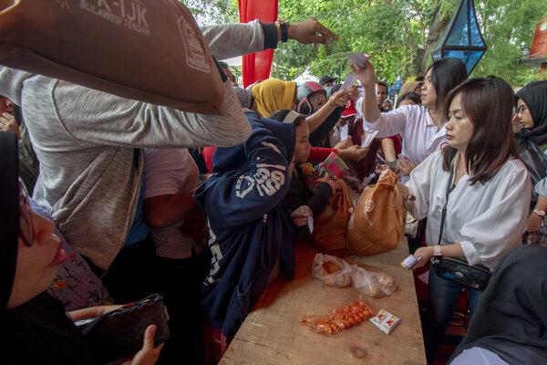 Petugas melayani warga yang membeli paket sembako pada Pasar Murah Otoritas Jasa Keuangan (OJK) dan Bank Indonesia (BI) di Palu, Sulawesi Tengah, Minggu (27/1/2019). - Antara/Basri Marzuki