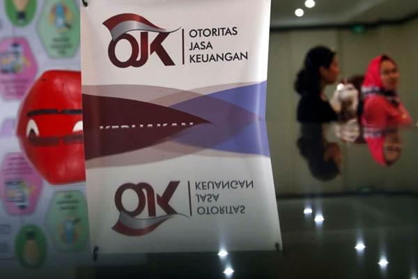 Karyawan melintas di dekat logo Otoritas Jasa Keuangan (OJK) di Jakarta - JIBI/Nurul Hidayat