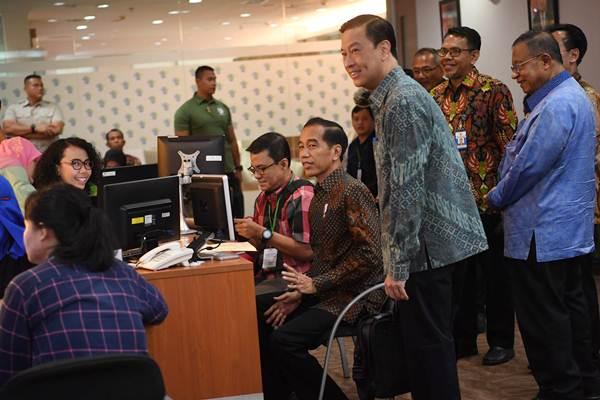 Presiden Joko Widodo (kanan duduk) didampingi Menko Perekonomian Darmin Nasution (kanan) dan Kepala BKPM Thomas Lembong (kedua kanan) meninjau layanan konsultasi Online Single Submission (OSS) BKPM di PTSP BKPM, Jakarta, Senin (14/1/2019). - ANTARA FOTO/Wahyu Putro A