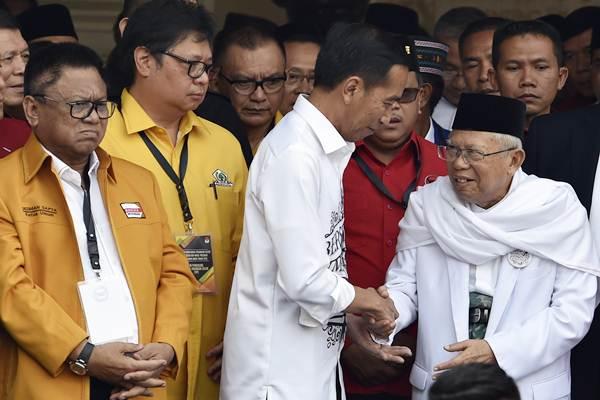 Calon presiden petahana Joko Widodo (tengah) menyalami calon wakil presiden Ma'ruf Amin (kanan), disaksikan Ketua Umum Hanura Oesman Sapta (kiri) dan Ketua Umum Golkar Airlangga Hartarto (kedua kiri) usai menyampaikan pidato politik di Gedung Joang, Jakarta, Jumat (10/8/2018). - ANTARA/Puspa Perwitasari