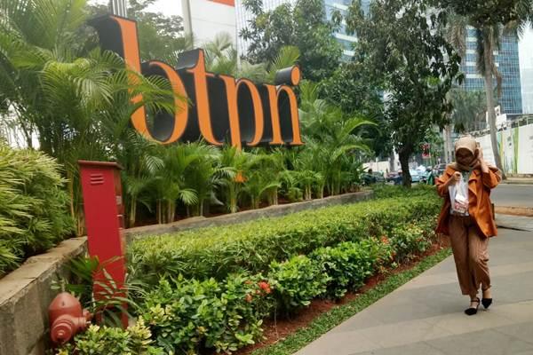 Pejalan kaki melintas di dekat logo PT Bank Tabungan Pensiunan Nasional Tbk. di Jakarta, Selasa (16/10/2018). - JIBI/Dedi Gunawan