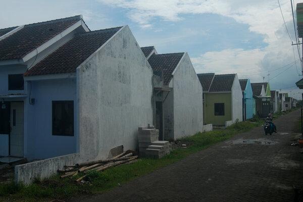Warga mengendarai motornya melintas di sebuah kompleks perumahan KPR bersubsidi di Tambak Beras, Jombang, Jawa Timur, Jumat (25/1/2019). Kementerian Pekerjaan Umum dan Perumahan Rakyat (PUPR) mengusulkan kenaikan harga rumah bersubsidi yang menggunakan skema Fasilitas Likuiditas Pembiayaan Perumahan (FLPP) sebesar tiga hingga 7,75 persen akibat adanya kenaikan harga material bangunan dan upah pekerja. - Antara/Syaiful Arif