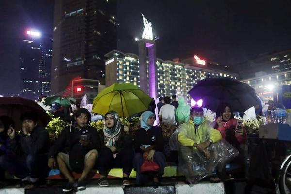 Warga menunggu pergantian Tahun Baru 2019 di kawasan Bundaran Hotel Indonesia, Jakarta, Senin (31/12/2018). - Bisnis/Felix Jody Kinarwan