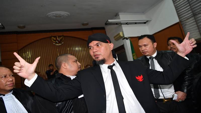 Terpidana kasus ujaran kebencian Ahmad Dhani mengacungkan kedua tangan seusai menjalani sidang putusan di Pengadilan Negeri Jakarta Selatan, Jakarta, Senin (28/1/2019). Majelis hakim memvonis Ahmad Dhani dengan hukuman satu tahun enam bulan penjara, dan atas putusan hakim tersebut kejaksaan langsung menahan terpidana. ANTARA FOTO - Sigid Kurniawan.