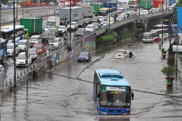 Busway menerobos genangan air di Grogol, Jakarta, Selasa (21/2). - JIBI/Abdullah Azzam