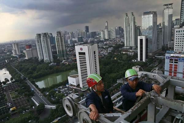 Pekerja melakukan perawatan rutin pada salah satu gedung bertingkat di Jakarta - JIBI/Nurul Hidayat