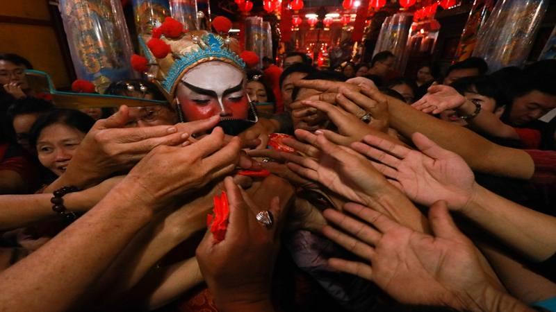 Pria berkostum Dewa Rejeki (tengah) membagikan angpao pada warga setelah pelaksanaan sembahyang tahun baru Imlek 2570 di Klenteng Hong San Ko Tee, Surabaya, Jawa Timur, Selasa (5/2/2019). Bagi-bagi angpao itu merupakan salah satu tradisi yang dilakukan saat perayaan tahun baru Imlek. - Antara