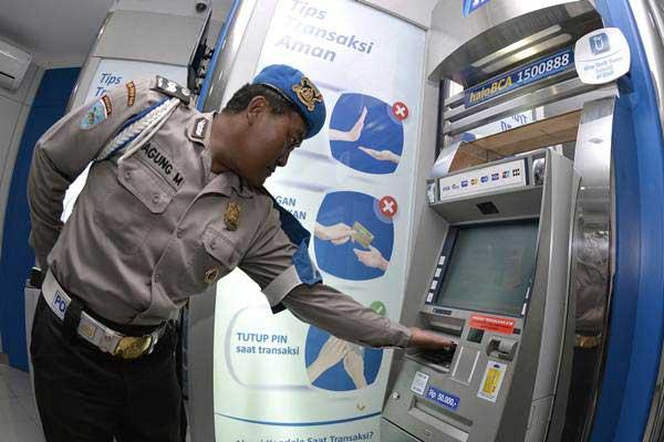 Petugas kepolisian memeriksa mesin Anjungan Tunai Mandiri (ATM) di sebuah pusat perbelanjaan di kawasan Kuta, Bali, Senin (26/3/2018). - ANTARA/Fikri Yusuf