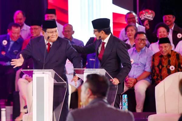Pasangan nomor urut 02 Capres Prabowo Subianto (kiri) melakukan gerakan menari, disaksikan Cawapres Sandiaga Uno saat mengikuti debat pertama Pilpres 2019, di Hotel Bidakara, Jakarta, Kamis (17/1/2019). - Bisnis/Abdullah Azzam