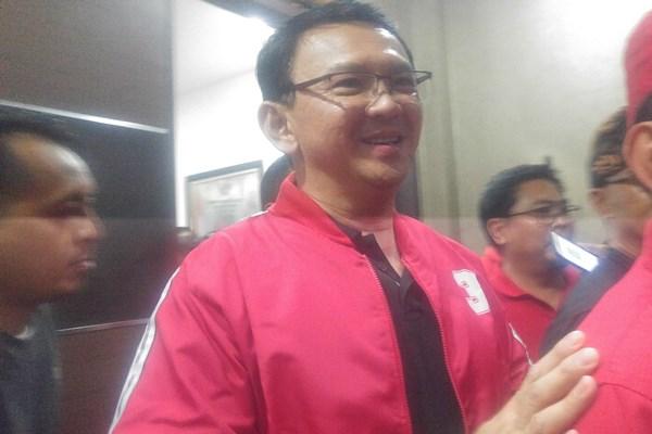 Basuki Tjahaja Purnama atau Ahok keluar dari salah satu ruangan di PDIP Bali, Jumat (8/2) dengan menggunakan jaket merah dengan gambar angka 3 di dada bagian kiri dan tulisan PDIP pada belakang jaket untuk menegaskan posisinya yang telah resmi menjadi anggota partai banteng tersebut. (Ni Putu Eka Wiratmini - Bisnis)
