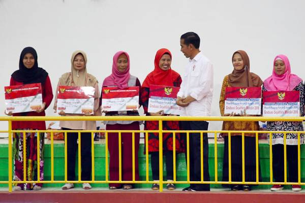 Presiden Joko Widodo (ketiga kanan) menyapa warga saat acara penyaluran Dana Bantuan Sosial Non Tunai Program Keluarga Harapan (PKH) kepada Keluarga Penerima Manfaat (KPM), di Jakarta, Kamis (10/1/2019). - Bisnis/Abdullah Azzam