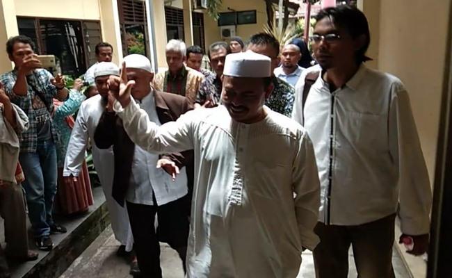 Ketua Umum Persaudaraan Alumni (PA) 212 Slamet Ma'arif mengacungkan jari telunjuk dan ibu jarinya saat berjalan menuju ruang penyidik Satreskrim Polresta Surakarta, Kamis (7/2/2018). - Solopos/Kurniawan