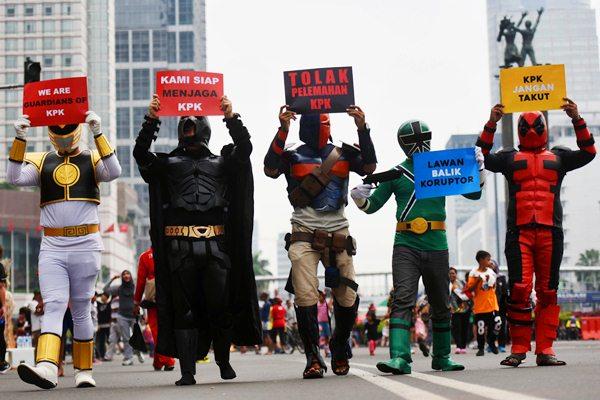 Pegiat dari Koalisi Save KPK mengenakan kostum super hero saat menggelar aksi dukungan kepada KPK, di Jakarta, Minggu (16/4). - Antara/Akbar Nugroho Gumay