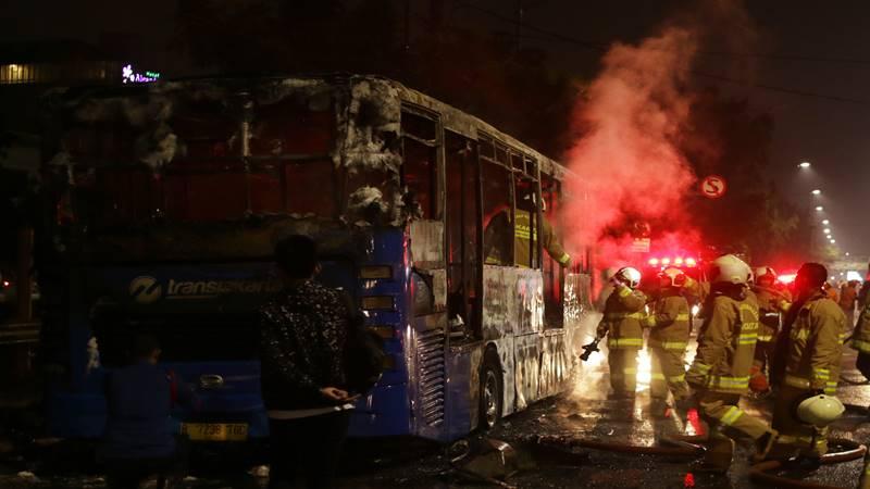 Petugas melakukan pendinginan seusai memadamkam api pada Bus Transjakarta yang terbakar di Jalan Pos Besar, Pasar Baru, Jakarta, Senin (18/2/2019). Penyebab kebakaran Bus Transjakarta tersebut masih dalam tahap penyelidikan petugas. - Antara