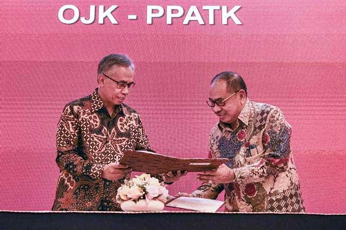Ketua Dewan Komisioner OJK Wimboh Santoso (kiri) bersama Ketua PPATK Kiagus Ahmad Badaruddin (kanan) melakukan penandatanganan nota kesepahaman (MoU) di Jakarta, Selasa (19/2/2019). - ANTARA/Hafidz Mubarak A