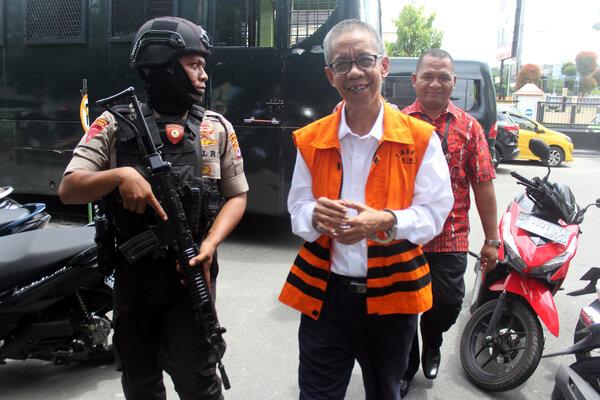 Mantan Kepala Kantor Pelayanan Pajak (KPP) Pratama Ambon, La Masikamba (menggunakan rompi) dikawal personil Brimob saat hendak menjalani sidang perdana perkara gratifikasi dan suap wajib pajak yang digelar di Pengadilan Tipikor Ambon, Maluku, Selasa (19/2/2019). La Masikamba didakwa telah menerima gratifikasi sebesar Rp7,8 miliar dari wajib pajak sejak tahun 2016 - 2018. - Antara/Izaac Mulyawan