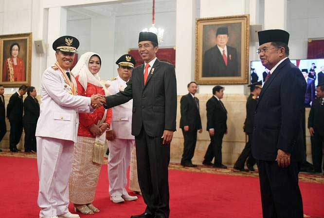 Presiden Joko Widodo (kedua kanan) didampingi Wakil Presiden Jusuf Kalla (kanan) berjabat tangan dengan Gubernur Riau yang baru dilantik Syamsuar (kiri) dan Wakil Gubernur Riau Edi Natar Nasution (ketiga kiri) di Istana Negara, Jakarta, Rabu (20/2/2019). - ANTARA FOTO/Akbar Nugroho Gumay