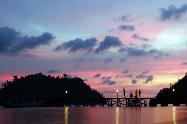 Wisatawan menikmati matahari terbenam di pantai Baga, Kawasan Wisata Bahari Terpadu (KWBT) Mandeh, Pesisir Selatan, Sumatera Barat, Rabu (30/1/2019). Kementerian Pekerjaan Umum dan Perumahan Rakyat (PUPR) telah merampungkan pembangunan jalan akses sepanjang 41,08 km ke KWBT Mandeh dan kini tempat tersebut dapat dicapai dalam 1-1,5 jam dari kota Padang. - Antara/Iggoy el Fitra