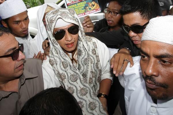 Habib Bahar bin Smith (tengah) memasuki gedung saat akan menjalani pemeriksaan di Bareskrim Polri, Jakarta, Kamis (6/12/2018). Habib Bahar diperiksa sebagai saksi terlapor terkait video ceramahnya yang dianggap menghina Presiden Joko Widodo. - ANTARA/Rivan Awal Lingga