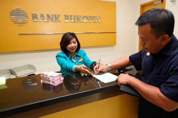 Karyawati melayani nasabah, di kantor Cabang Bank Bukopin di Jakarta, Senin (9/4/2018). - JIBI - Abdullah Azzam