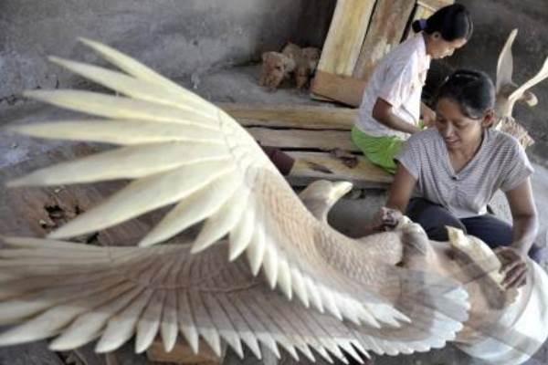 Dua perajin menyelesaikan proses akhir dari pembuatan kerajinan patung rajawali di Desa Pering, Gianyar, Bali, Kamis (22/9/2013). - Antara/Nyoman Budhiana