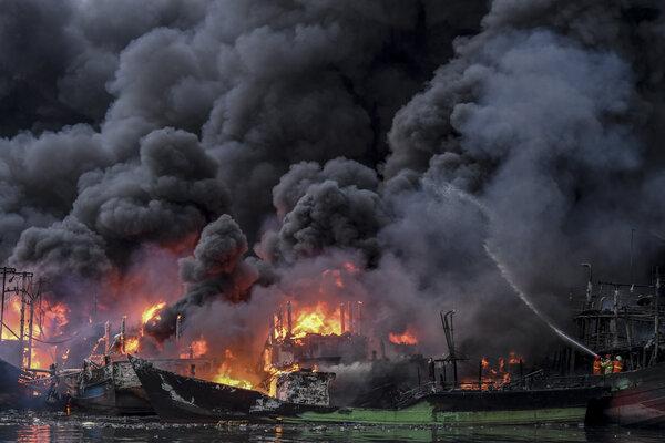 Petugas kebakaran berusaha memadamkan api yang membakar kapal-kapal nelayan di Pelabuhan Muara Baru, Jakarta, Sabtu (23/2/2019). - Antara/Hafidz Mubarak A