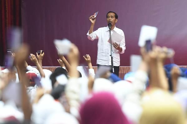Presiden Joko Widodo saat penyerahan Kartu Indonesia Pintar dan Program Keluarga Harapan di Gor Tri Dharma, Gresik, Jawa Timur, Kamis (8/3/2018). - ANTARA/Zabur Karuru