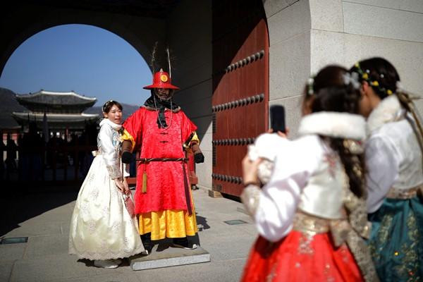 Turis menggunakan Hanbok, busana tradisional Korea, berfoto dengan penjaga yang menggunakan busana tradisional saat pergantian penjaga istana (royal guards) di Istana Gyeongbok, Seoul, Korea Selatan pada Senin (11/2/2019) - REUTERS/Kim Hong/Ji