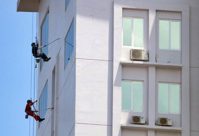 Pekerja mengecat dinding bangunan bertingkat - Bisnis/Paulus Tandi Bone