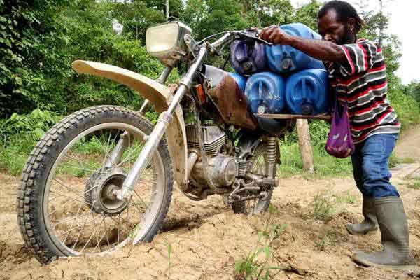 Warga membawa jerigen berisi BBM dengan motor melintasi jalan berlumpur di Keerom, Papua, Minggu (22/10). - ANTARA/Indrayadi TH