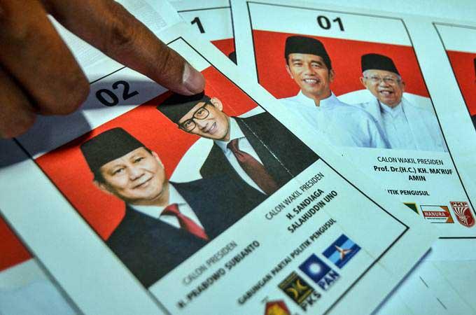 Petugas bagian sortir dan lipat surat suara menunjukan surat suara yang terdapat kerutan di surat suara Pilpres, di Gudang Logistik KPU Kota Tasikmalaya, Jawa Barat, Selasa(19/2/2019). - ANTARA/Adeng Bustomi