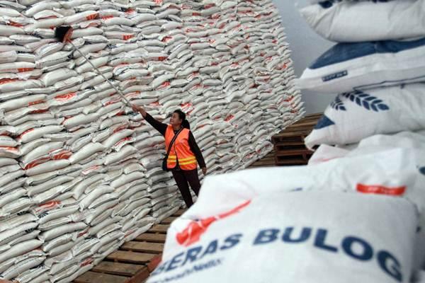 Pekerja membersihkan gudang beras Bulog Divre Sulselbar di Makassar, Sulawesi Selatan, Rabu (13/6/2016). - Bisnis.com/Paulus Tandi Bone