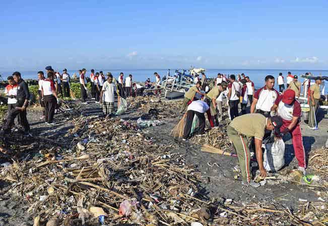 Sejumlah anggota Polda NTB membersihkan sampah di pinggiran pantai saat aksi bersih pantai di Tanjung Karang, Mataram, NTB, Kamis (21/2/2019). - ANTARA/Ahmad Subaidi