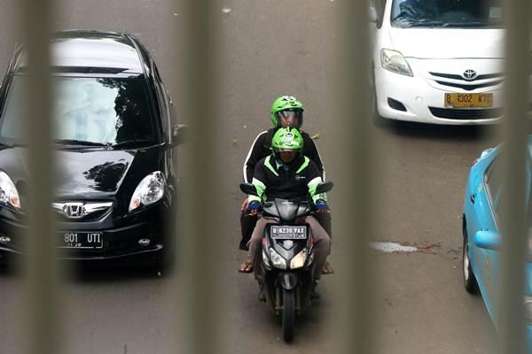 Pengemudi ojek berbasis online mengantar penumpang di kawasan Palmerah, Jakarta, Jumat (18/12). - Antara
