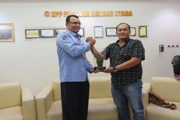Kepala KPP Pratama Malang Utara Heru Pamungkas Wibowo (kiri) bertukar cinderamata dengan Ketua PWI Malang Arieful Huda di Malang, Rabu (27/2/2019). - Istimewa