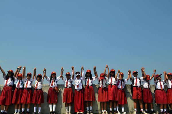 Sejumlah siswa SD bergandengan tangan bersama saat kegiatan Memeluk Jatigede 2018 di Bendungan Jatigede, Kabupaten Sumedang, Jawa Barat, Rabu (2/5). Kegiatan yang diikuti 30 ribu peserta dari siswa SD, SMP, serta guru se-Kabupaten Sumedang tersebut dalam rangka memperingati Hari Pendidikan Nasional. - Antara