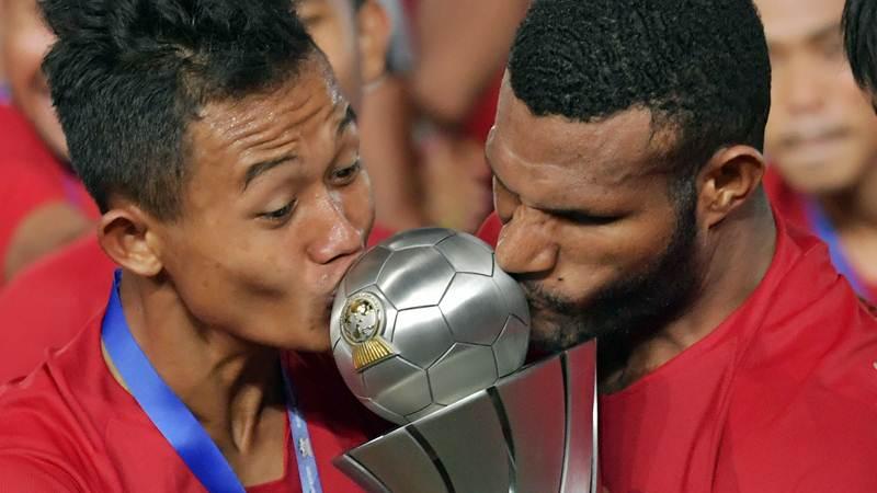 Pemain Timnas U-22 Sani Riski Fauzi (kiri) bersama Marinus Wanewar (kanan) mencium Piala AFF U-22 seusai penganugerahan piala di Stadion Nasional Olimpiade Phnom Penh, Kamboja, Selasa (26/2/2019). - ANTARA/Nyoman Budhiana