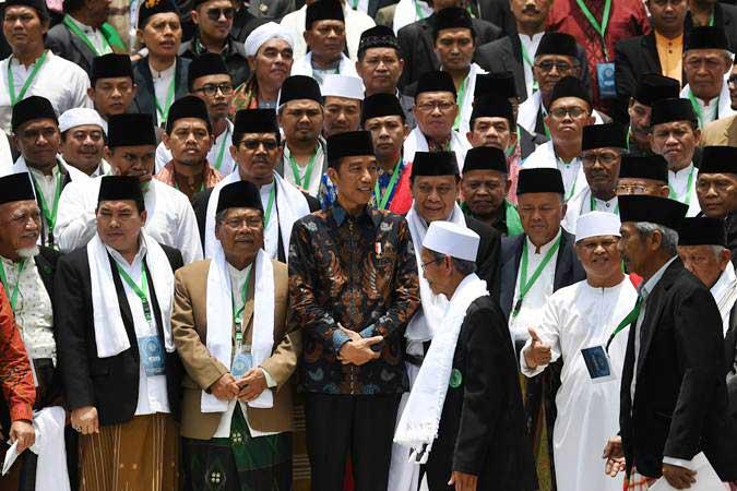 Presiden Joko Widodo (tengah) berfoto dengan sejumlah ulama saat acara silaturahmi Halaqah Ulama dan Pimpinan Pondok Pesantren Jawa Barat Tahun 2019 di Istana Negara, Jakarta, Kamis (28/2/2019). - ANTARA/Wahyu Putro A
