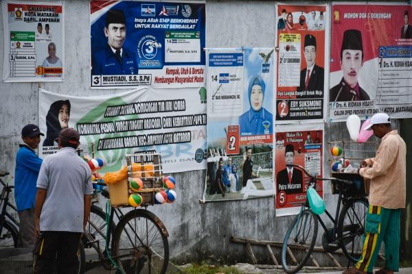 Sejumlah pedagang mainan balon berada dekat Alat Peraga Kampanye (APK) Calon Legislatif (Caleg) yang terpasang di bangunan kawasan kota tua Ampenan, Mataram, NTB, Senin (11/2/2019). - ANTARA/Ahmad Subaidi