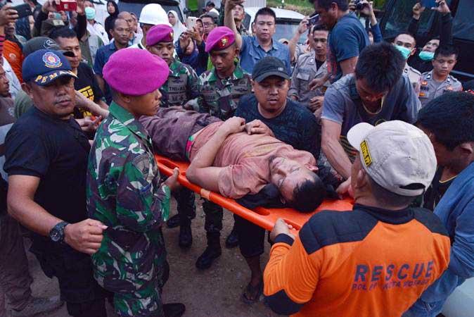 Petugas menggotong salah seorang penambang yang selamat dari lokasi Pertambangan Emas Tanpa Izin (PETI) Desa Bakan, Kecamatan Lolayan, Kabupaten Bolaang Mongondouw, Sulawesi Utara, Rabu (27/2/2019). - ANTARA/Adwit B Pramono