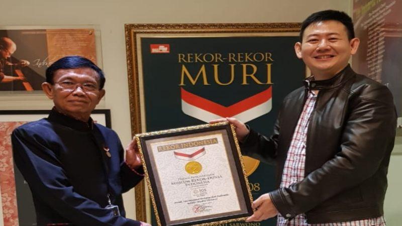 Senior Manager MURI Yusuf Ngadri (kiri) menyerahkan piagam MURI kepada Direktur PT IGS Benny Muliawan,