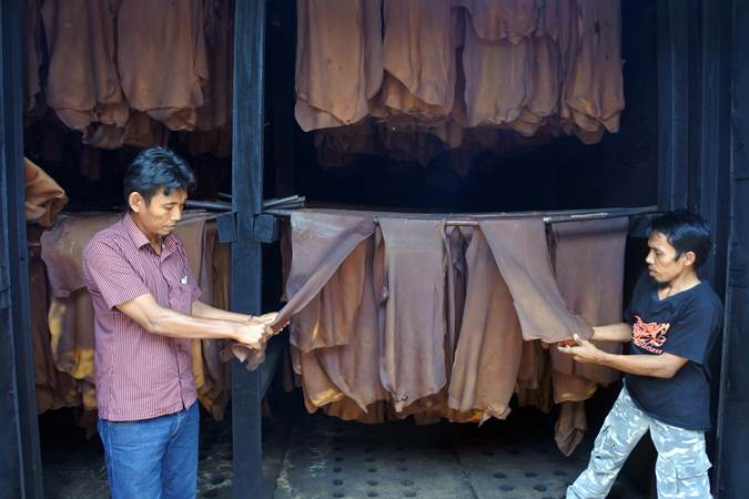 Pekerja melakukan proses pengasapan karet di pabrik pengolahan karet Kebun Glantangan milik PTPN XII, di Tempurejo, Jember, Jawa Timur, Minggu (3/3/2019). - ANTARA/Seno