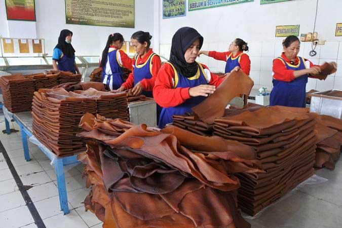 Sejumlah pekerja melakukan sortasi karet di pabrik pengolahan karet Kebun Glantangan milik PTPN XII, di Tempurejo, Jember, Jawa Timur, Minggu (3/3/2019). - ANTARA/Seno