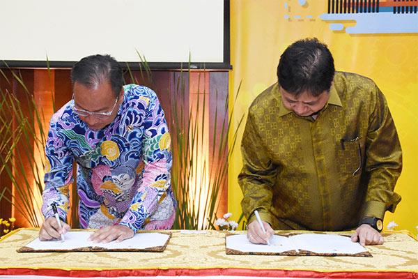 Menteri Perindustrian Airlangga Hartarto bertukar cenderamata dengan Menteri Sosial Agus Gumiwang Kartasasmita usai melakukan penandatanganan Nota Kesepahaman antara Kementerian Perindustrian dan Kementerian Sosial di Jakarta, 8 Maret 2018.