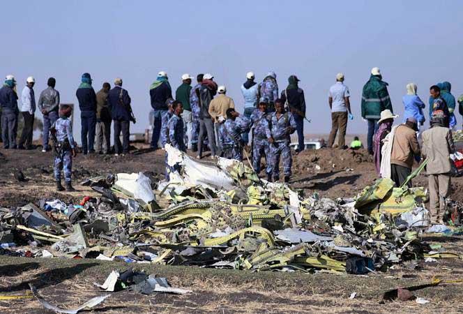 Polisi berdiri di lokasi jatuhnya pesawat Ethiopian Airlines dengan nomor penerbangan ET 302, di dekat Kota Bishoftu, 62 kilometer dari tenggara Ibukota Addis Ababa, Ethiopia, Minggu (10/3/2019). - REUTERS/Tiksa Negeri