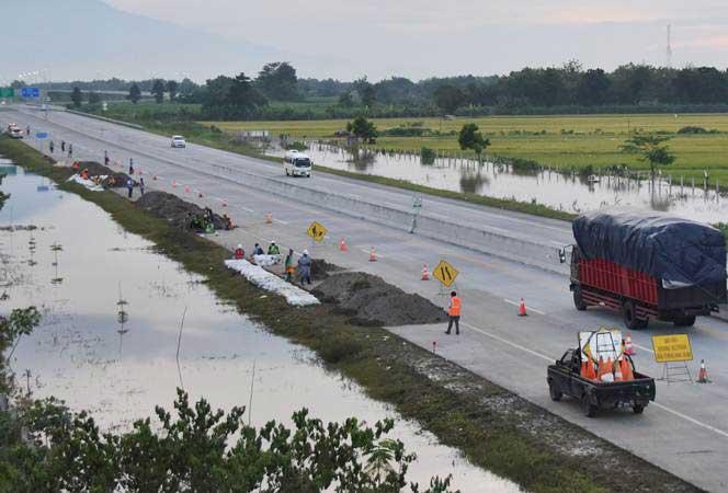 Pekerja menguruk tepi jalan tol Trans Jawa ruas Ngawi-Kertosono yang sebelumnya terendam banjir, kini  sudah normal kembali, di Desa Glonggong, Balerejo, Kabupaten Madiun, Jawa Timur, Jumat (8/3/2019). - ANTARA/Siswowidodo
