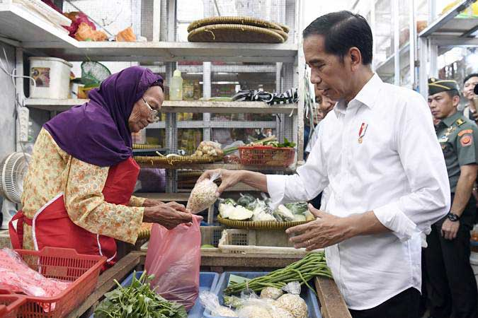 Presiden Joko Widodo (kanan) berbincang dengan pedagang saat meninjau barang kebutuhan pokok di Pasar Pelemgading, Cilacap, Jawa Tengah, Senin (25/2/2019). - ANTARA/Puspa Perwitasari