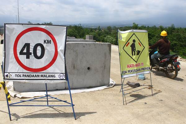 Pekerja melintas di pintu keluar jalan tol Pandaan-Malang di Karanglo, Malang, Jawa Timur, Rabu (19/12/2018). - ANTARA/Ari Bowo Sucipto