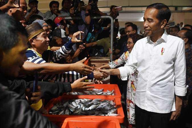 Presiden Joko Widodo (kanan) berjabat tangan dengan pedagang usai meresmikan Pasar Ikan Modern Muara Baru di Jakarta, Rabu (13/3/2019). - ANTARA/Akbar Nugroho Gumay