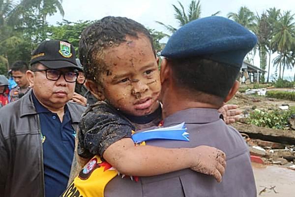 Seorang anak korban luka akibat tsunami digendong petugas, di Pandeglang, Provinsi Banten, Minggu (23/12/2018). - Reuters